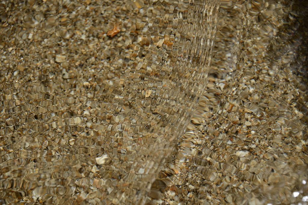 清流の流れが止められ、行き場を失った水が独特な水紋を気付き、それが砂粒のモザイクパターンを創り出す