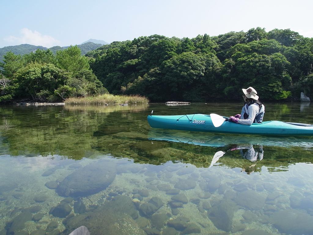 台風で一掃された美しい栗生川はどこまでも透明で、エメラルドグリーンの水面をカヤックにて進む参加者の写真
