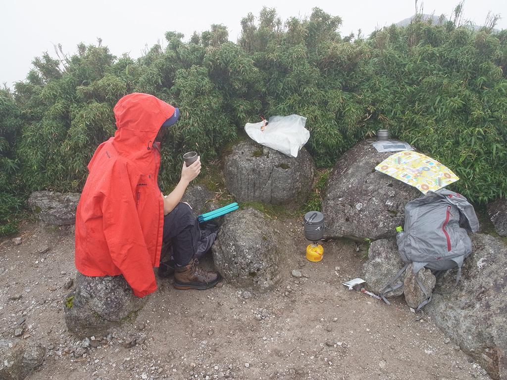 ガスに包まれて真っ白な山頂で、コーヒーを飲む参加者Mさんの写真