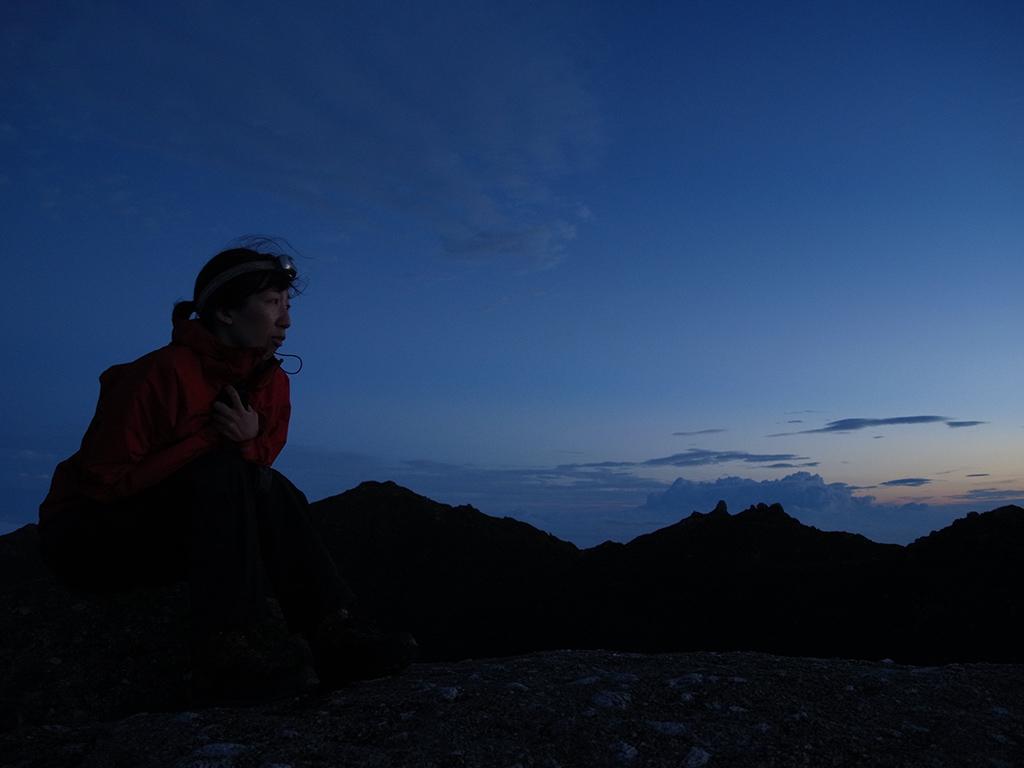 冷たい風が吹くため寒いので丸まるように座り、刻々と変わる景色を見続ける参加者Mさんのアップ写真