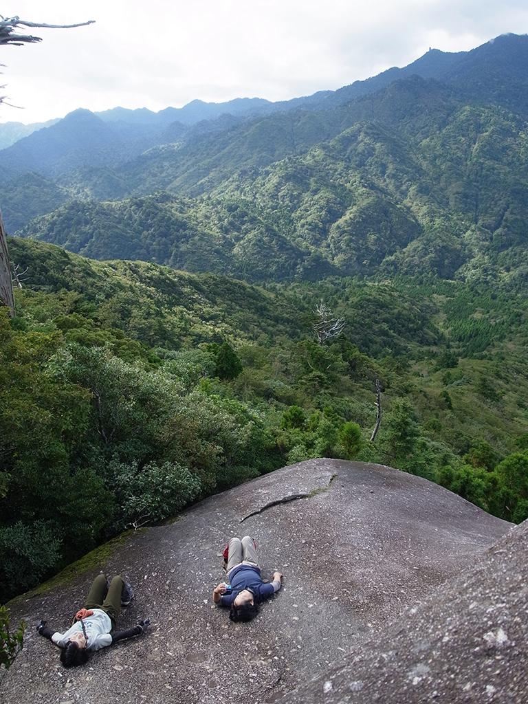屋久島の山々をバックに太鼓岩の上でゴロンと横になる二人の写真