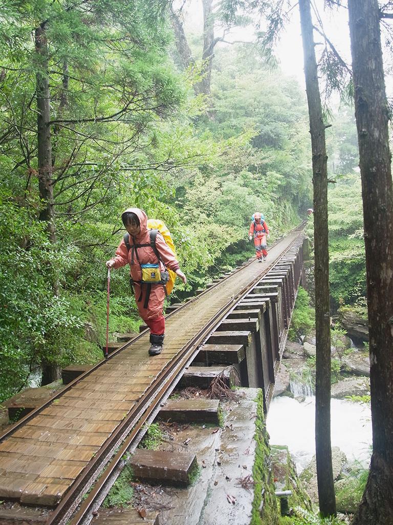 涸沢がしっかりとした水量の川となり、そこに架かる橋を怖々と渡るNさんと後ろのKさんの写真