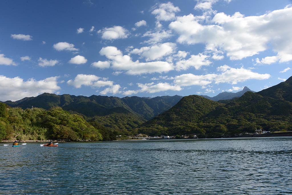 絶好の天気に恵まれた屋久島の栗生川で、広がる海と山をバックにカヤックを進めるファミリーの写真