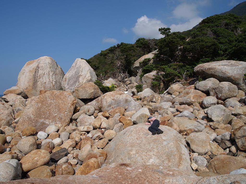 海岸線に転がる巨石の上で太陽の陽射しを感じてお昼寝中の参加者