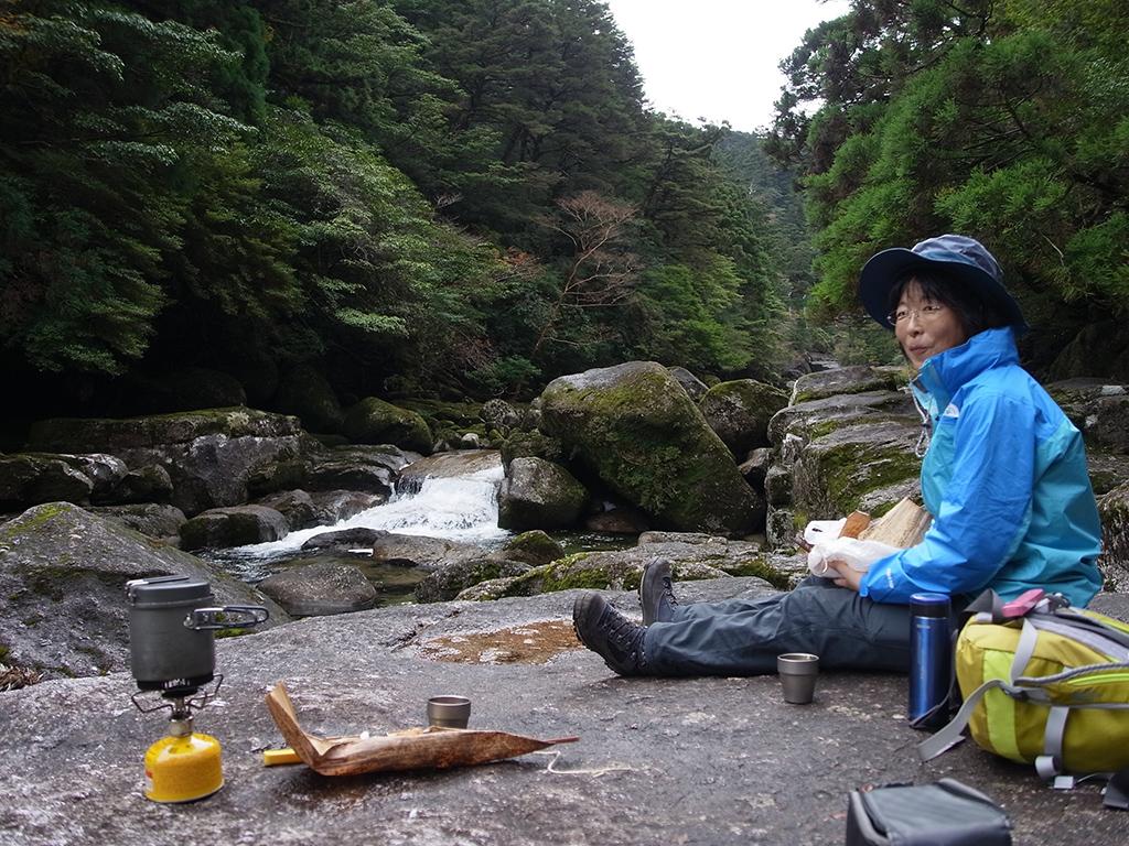 川原で竹皮に包まれたお弁当を広げて食べる参加者の写真