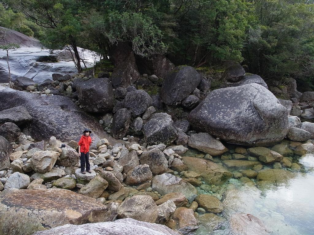 巨石とエメラルドグリーンに輝く透明な水に囲まれて立つ参加者の写真