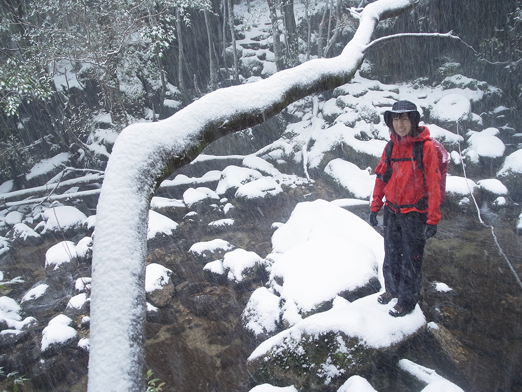 徒涉点で降りつける雪の中寒そうに立っている参加者の写真