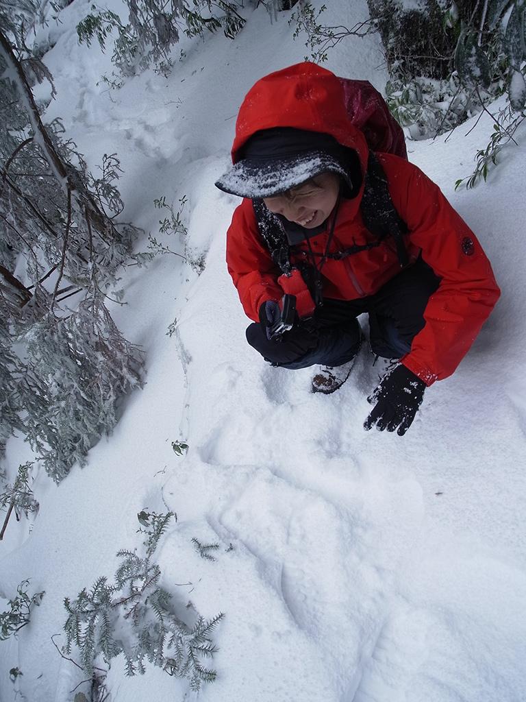 足元に積もる美しい新雪の写真を撮っている参加者の写真