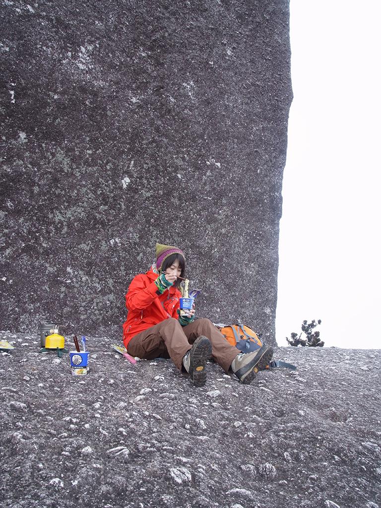太忠岳山頂に鎮座する巨岩・天忠石の前でポーズを取る参加者Tさんの写真