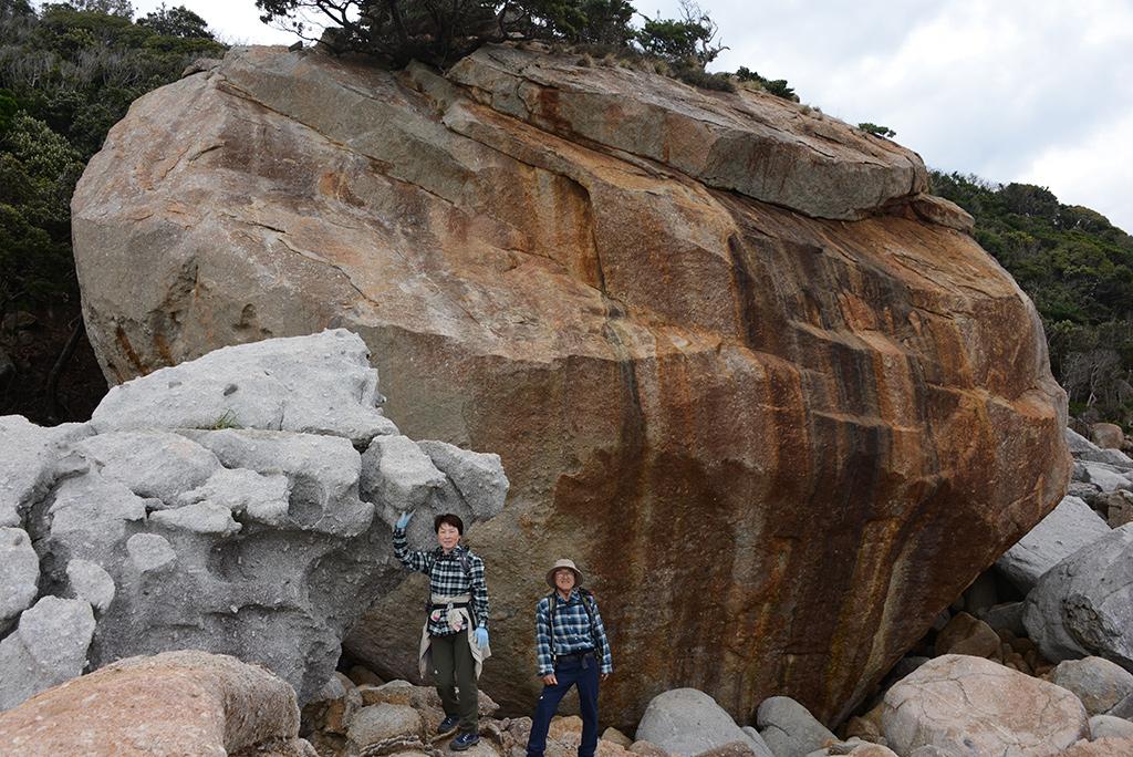 超巨大な花崗岩の巨石群の中に立ち尽くす二人の写真