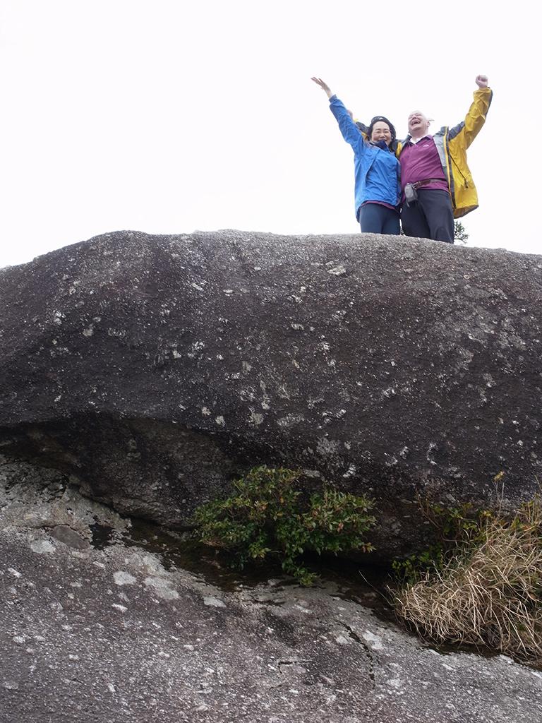 太鼓岩の上で、両腕を大きく広げて空を仰いでいる二人の写真