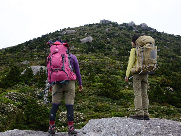 黒味岳の背後に廻り、投石平から黒味岳を仰ぎ見る大きなザックを背負った2人の写真