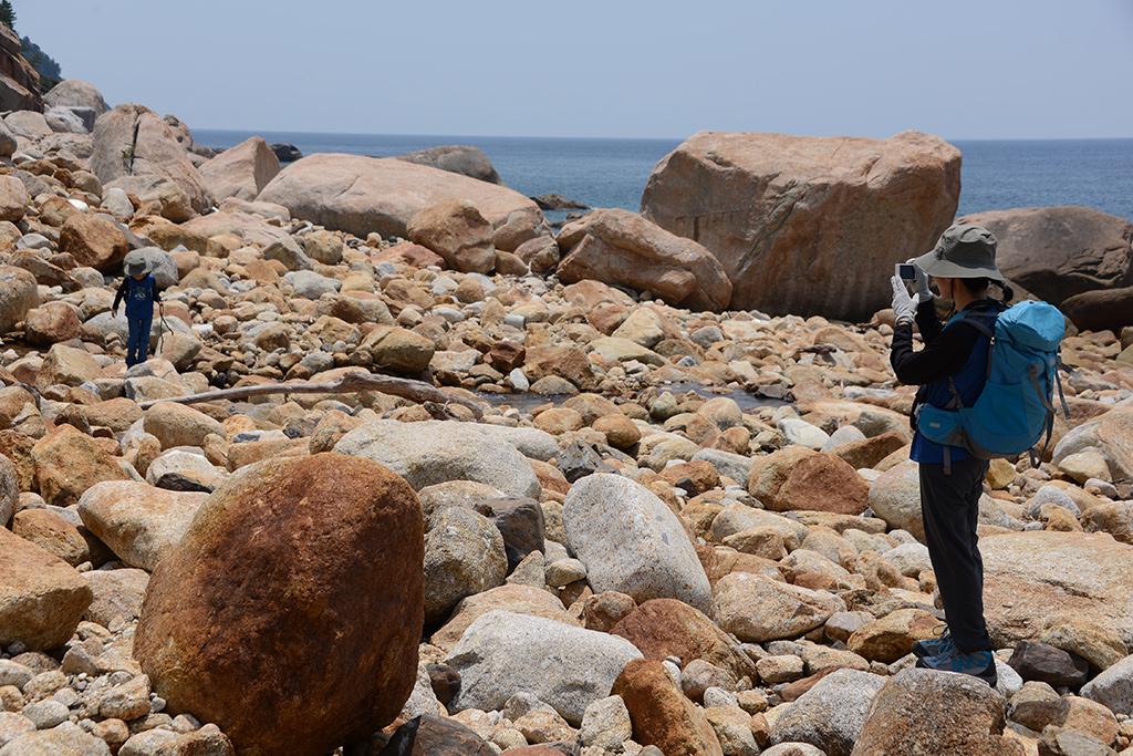 足場の悪い岩ゴロゴロの海岸線をあるくHちゃんとその姿を撮る母Mさん