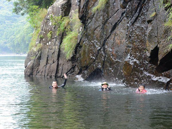 岩壁から落ちてくる石清水を水に浮かびながら体で受け止めて遊んでいる3人の写真