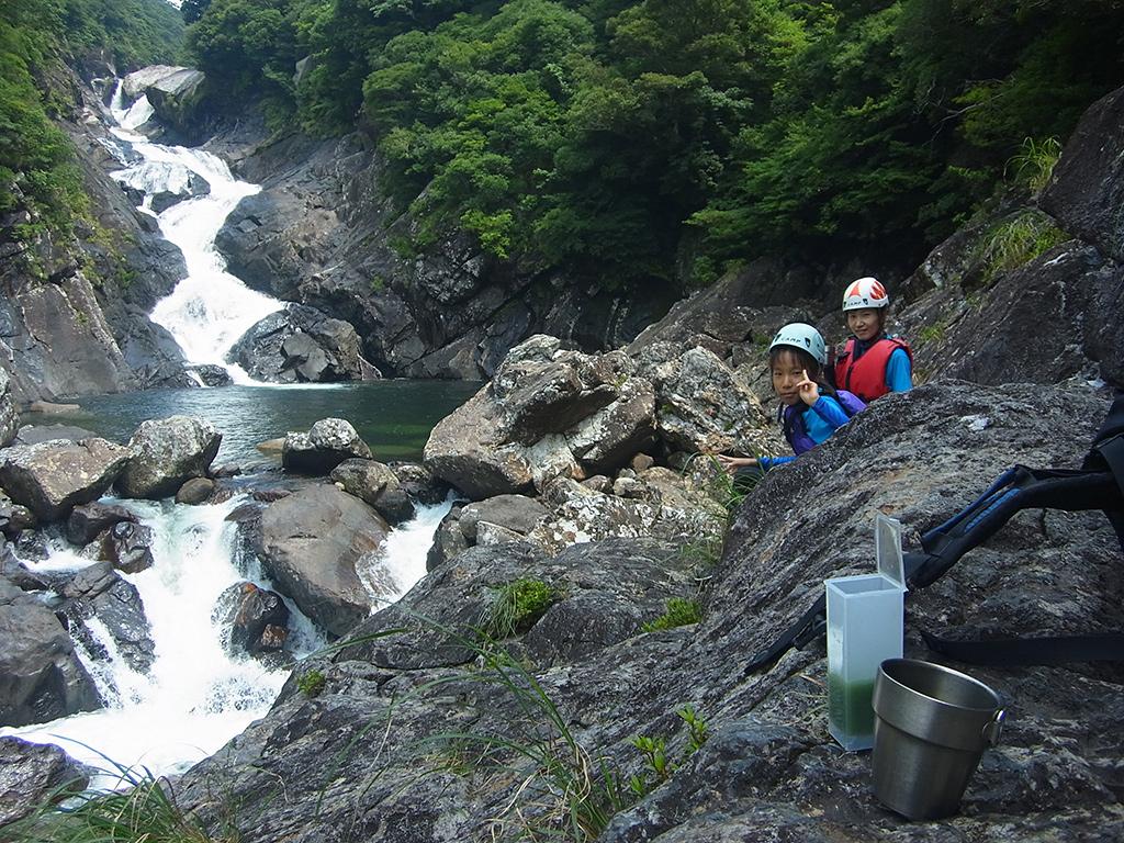 ゴールとなる滝の前で、美味しい抹茶水ようかんとコーヒーで幸せなひと時を過ごす二人の写真