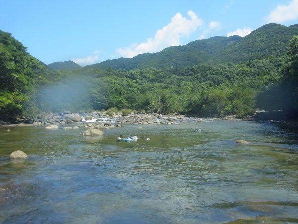 奥には山の緑と青空が映え、そこを流れる静かな流れに仰向けになって流れてくる二人の写真