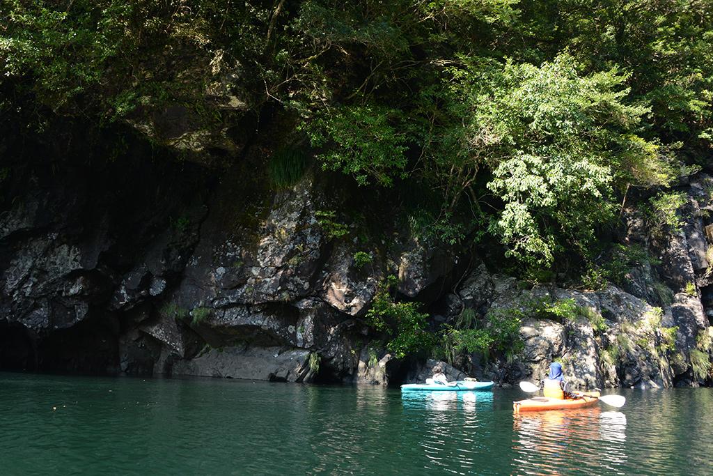 頭上にせり出す岩壁、目の前にカヤックが1艇だけ入る隙間がある穴を見つけて寄って行くお二人の写真