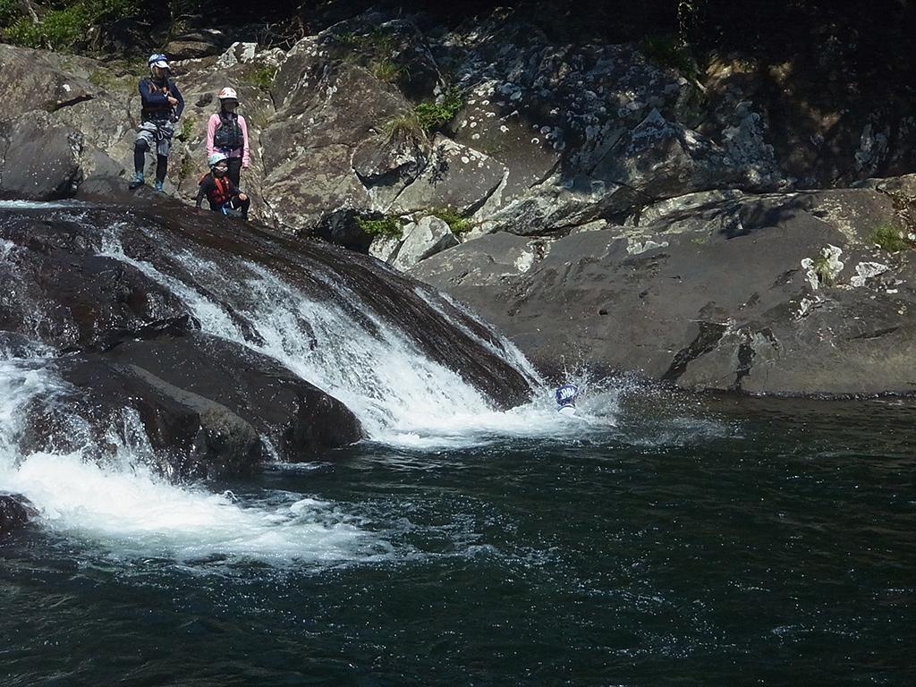 天然のウォータースライダーをして水に突っ込む長男のT君とそれを見守る家族の写真