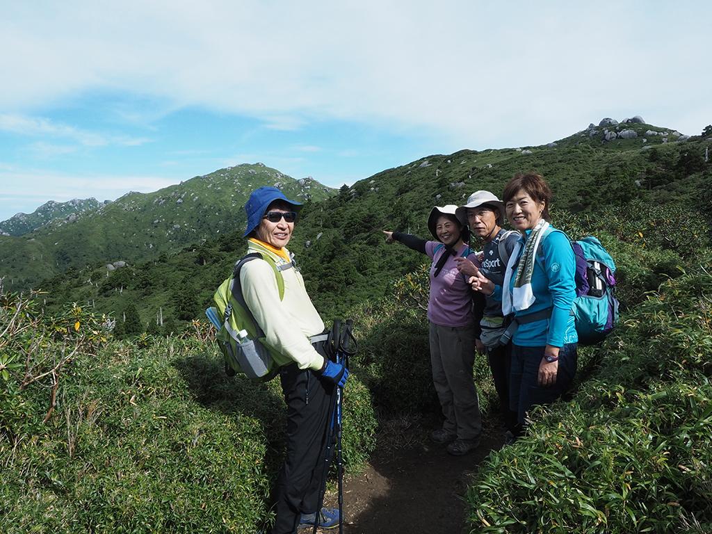 あそこに行きまーす!と遠くにある宮之浦岳を指さす参加者達の写真