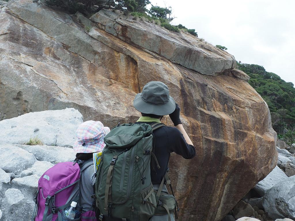 とてつもない巨石を前にする参加者二人の後ろ姿写真