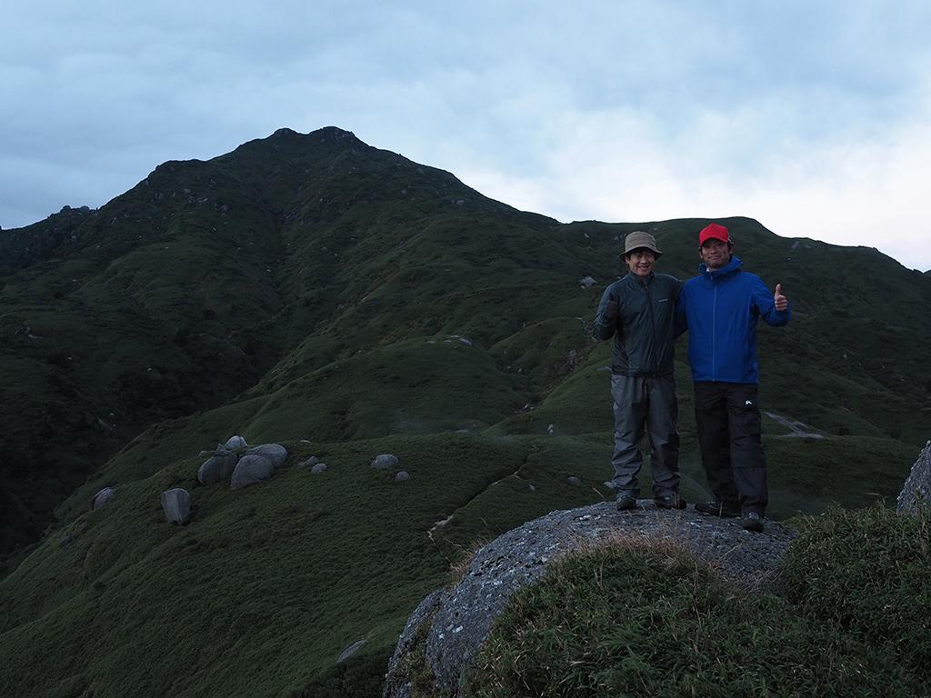 早朝の宮之浦岳をバックに笑顔に溢れるお二人の写真