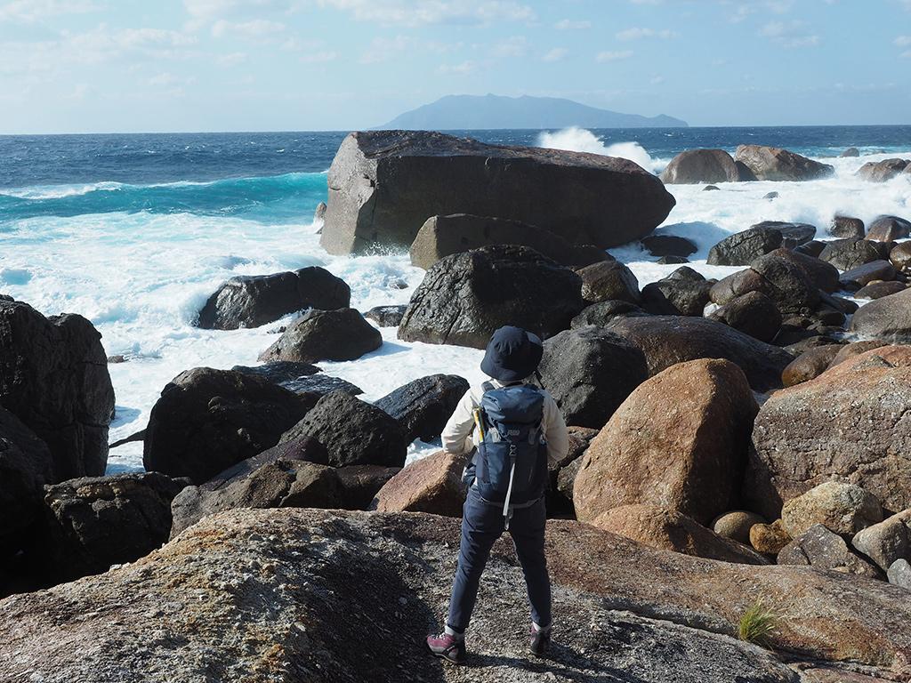 打ち寄せる波が巨石だらけの海岸に打ち付けては押し寄せる様子を見ている参加者Sサンの後ろ姿