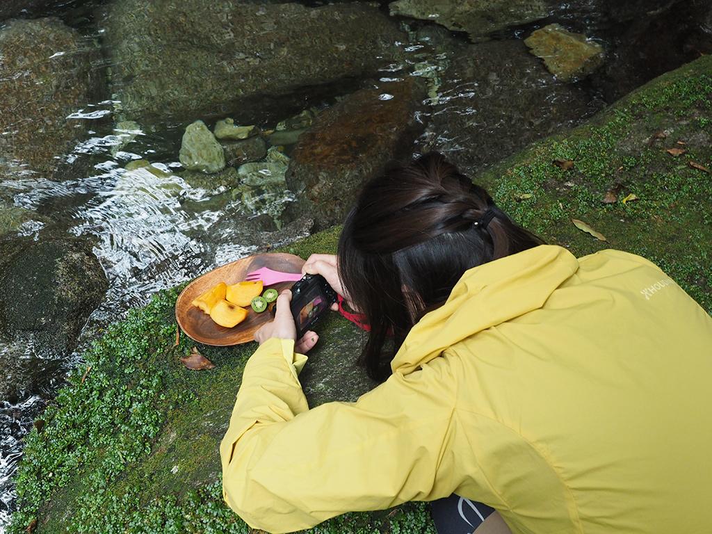 持参した柿と、ツアー中に見つけたキウイのようなシマサルナシの実をトレーに載せてフォトジェニックに撮っている参加者の写真