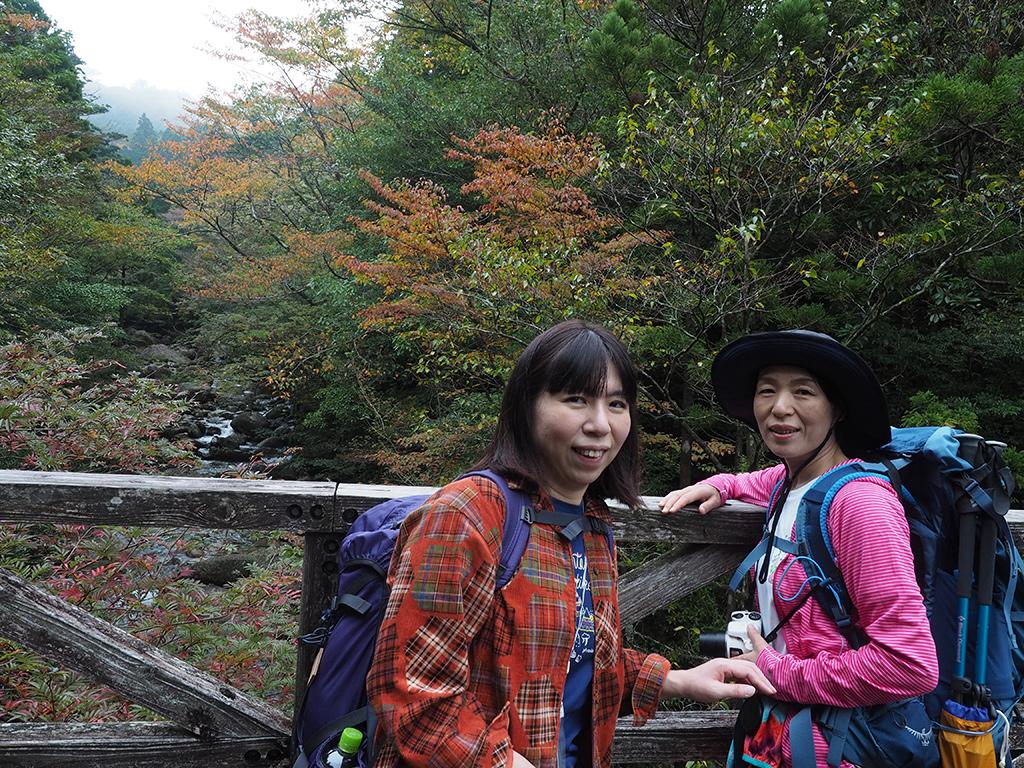 紅葉が始まった沢を背景に撮った二人の写真
