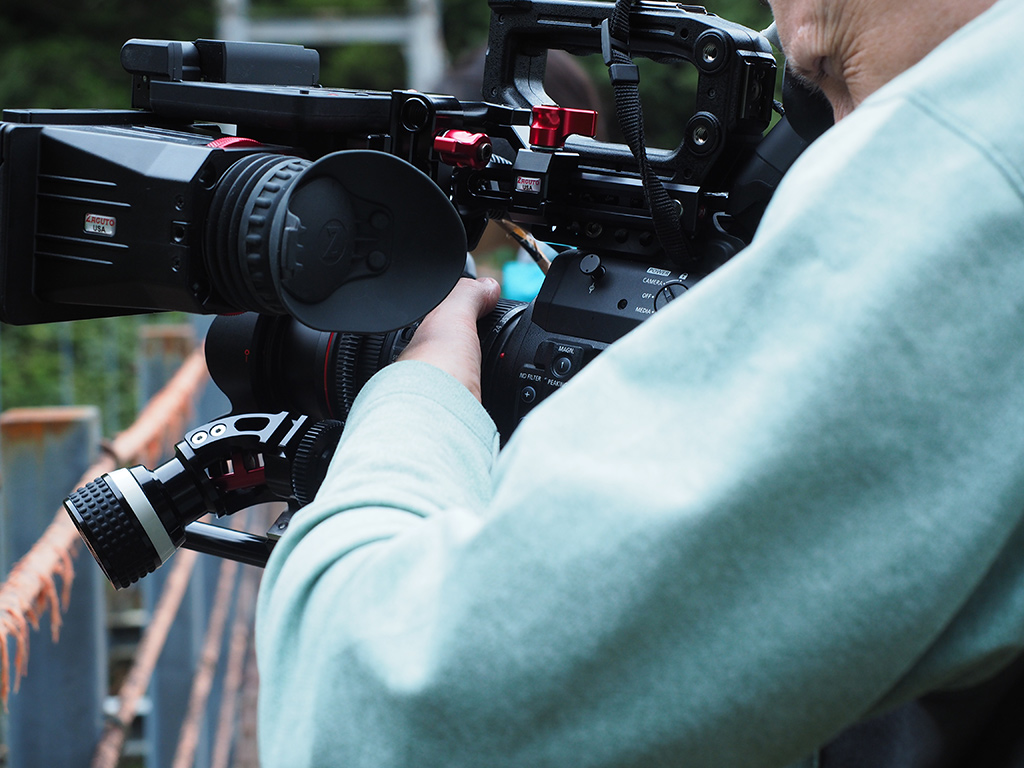 カメラ機材のアップとファインダーを真剣に覗き込むF氏の写真