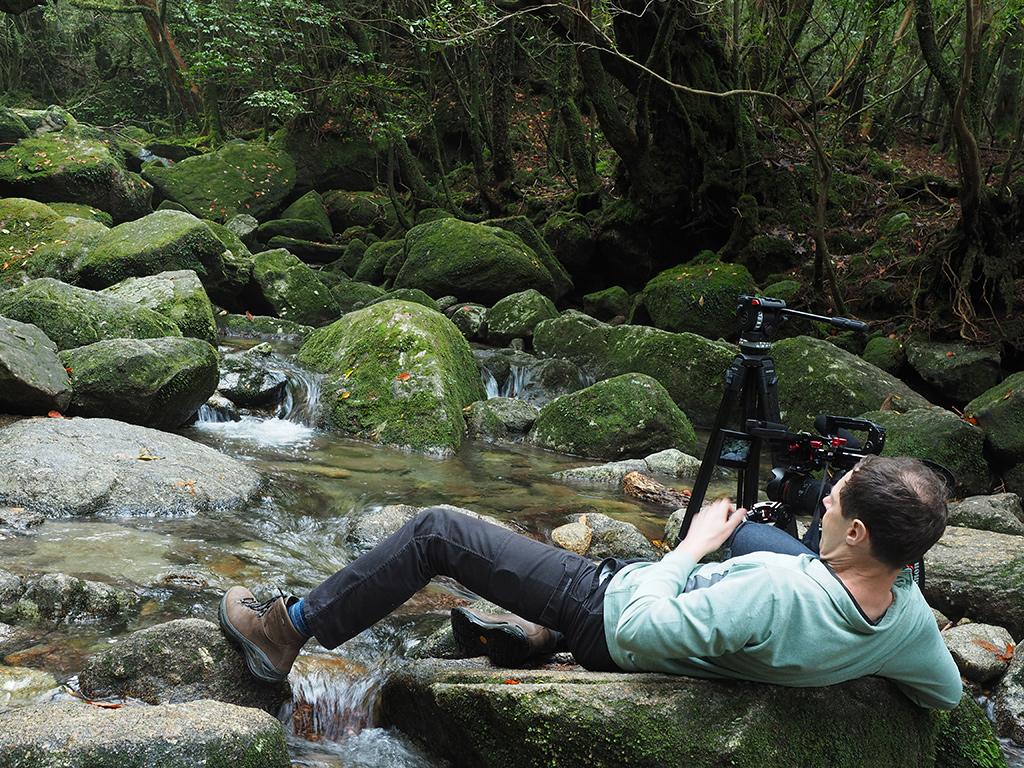 川の徒涉点にある飛び石に横たわり撮影機材に向かうF氏の写真