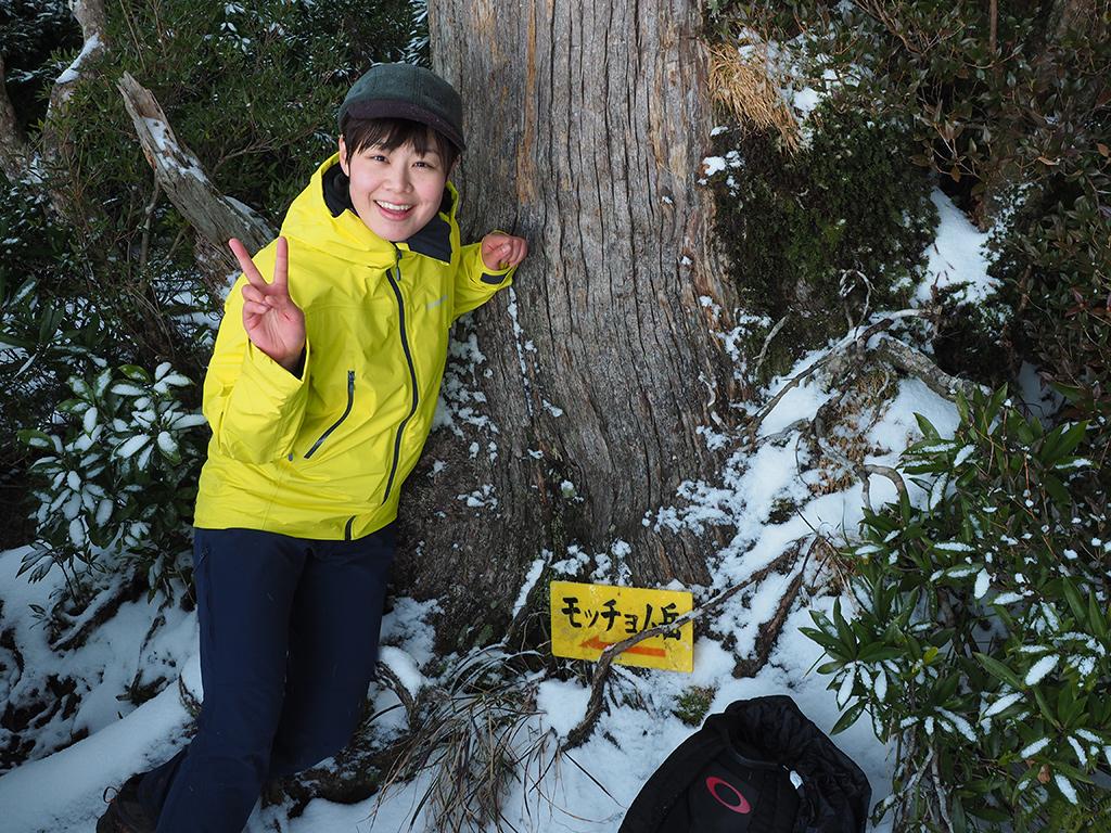 神山展望台にあるモッチョム岳を指し示す道標を横に、ピースサインをする参加者Kさんの写真