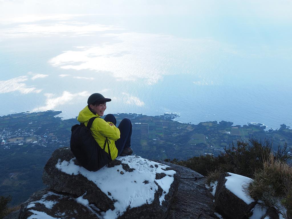 モッチョム岳の山頂に座り満面の笑みで振り返る参加者Kさんの写真