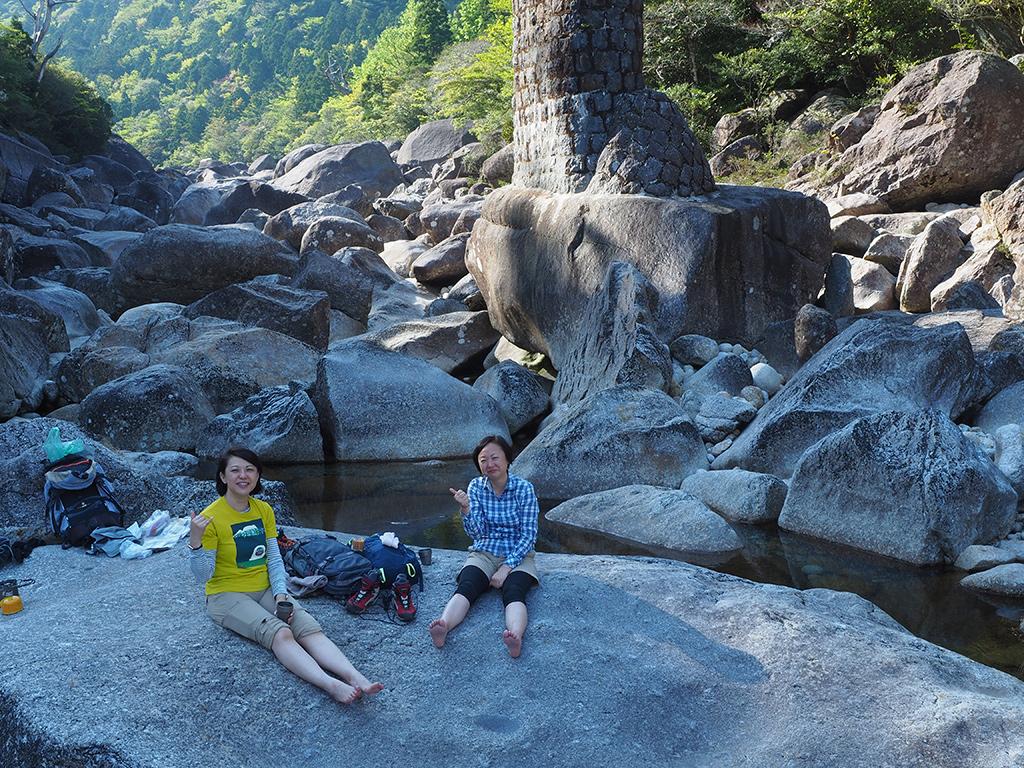 巨石だらけの河原でお茶タイムで、身も心も癒されている二人の写真
