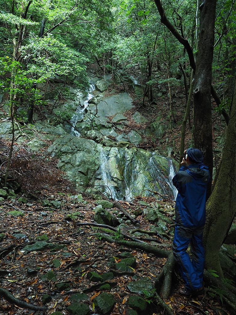 岩壁を流れ落ちる小さな滝を撮るOさんの写真
