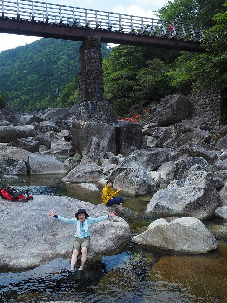 大きな川にゴロゴロする巨石に座って足を水に浸けてリラックスする二人の写真