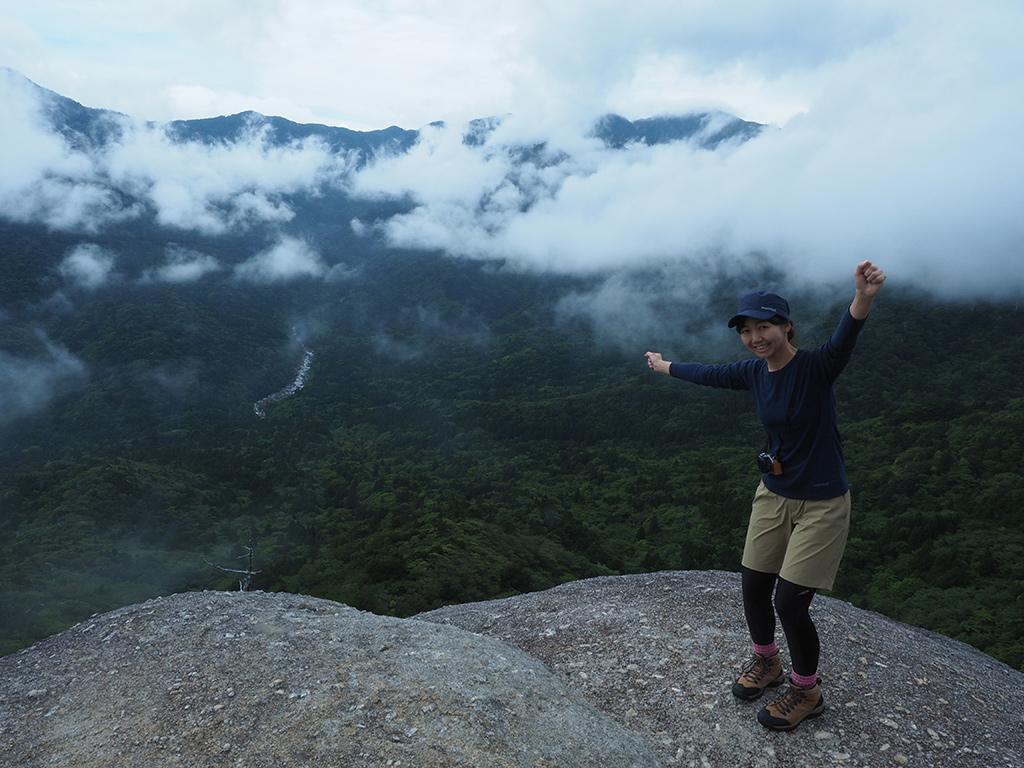 太鼓岩から見える雲と奥岳の絶景をバックに、手を広げてポーズをとる参加者Mさんの写真