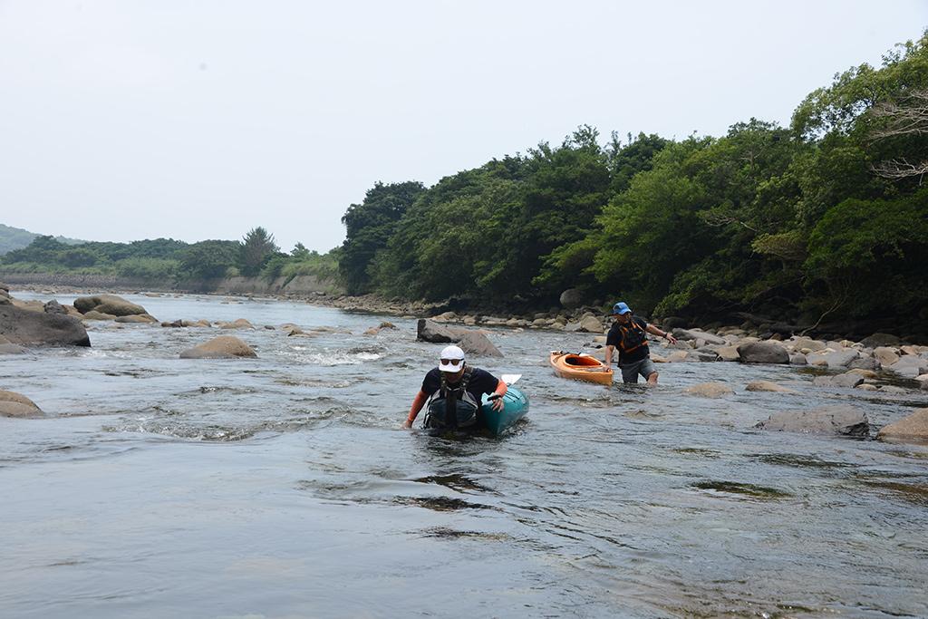 大潮の干潮で浅くなった川を歩いてカヤックを引っ張る2人の写真