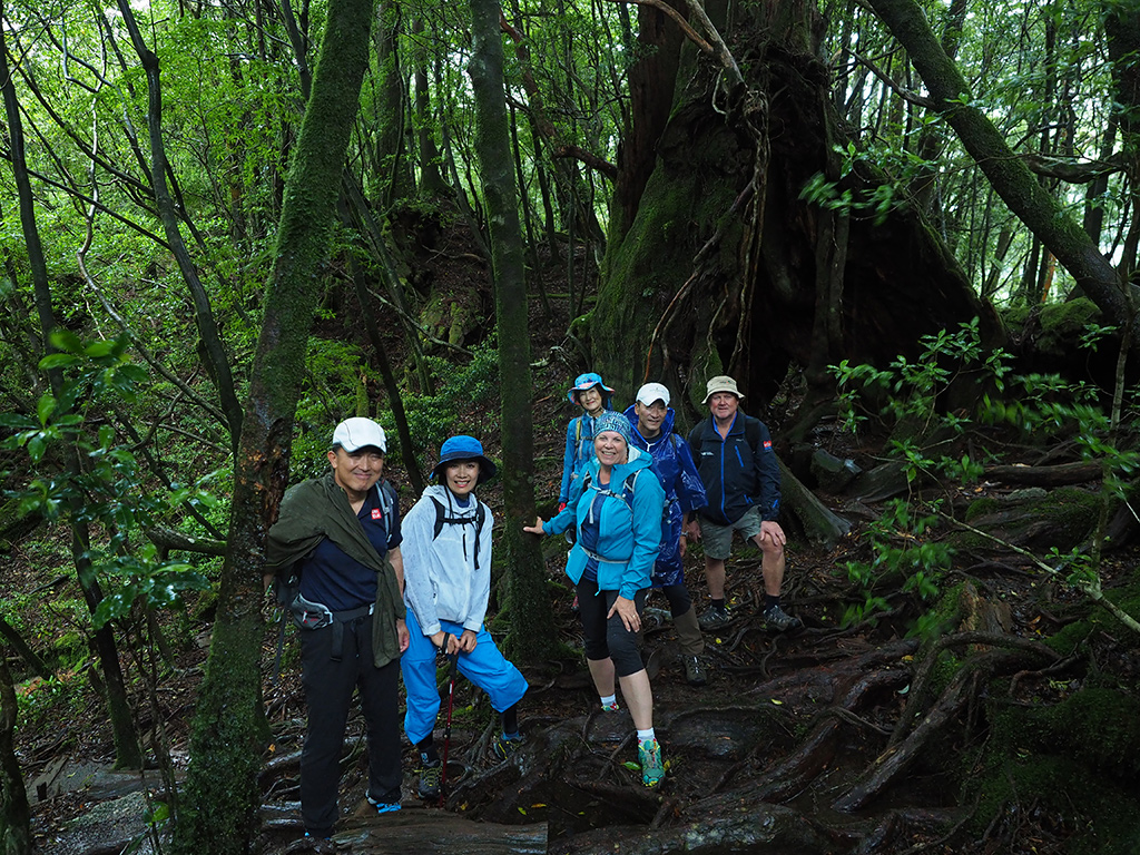 雨で濡れた森の中で6人の笑顔溢れる写真