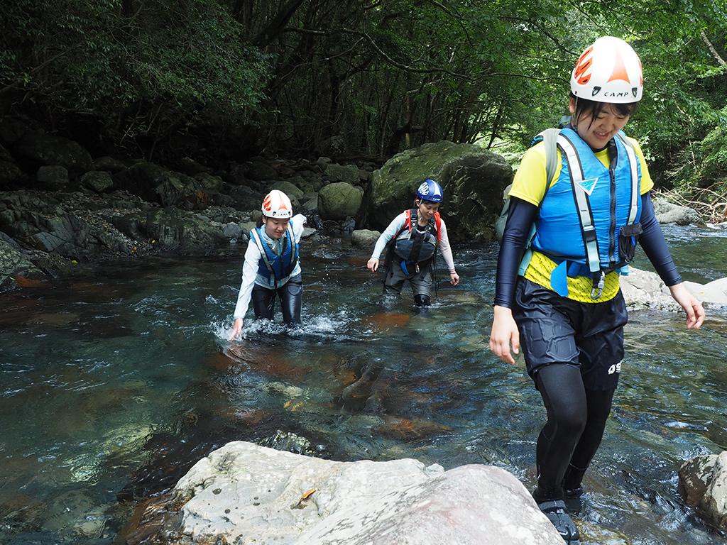 透き通る水の中を気持ち良さそうに歩く参加者の写真