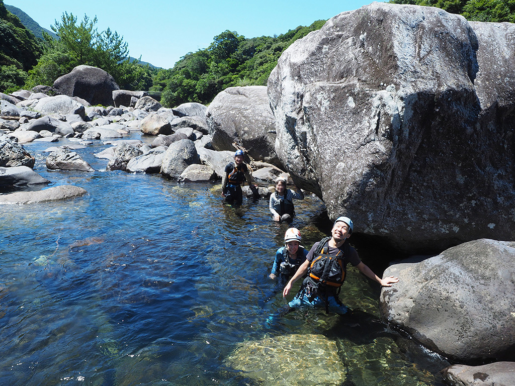 汗だくになりながら終えた準備体操後、川に入って濡れる幸せが全身で表現されている巨石と参加者4人の写真