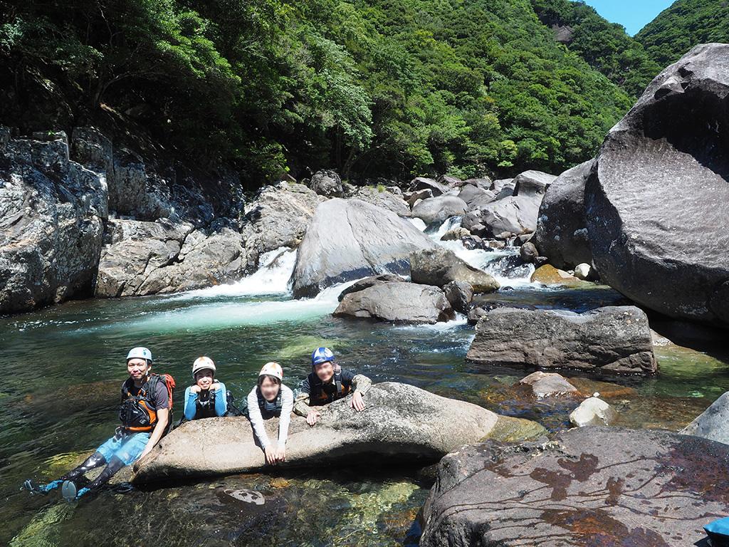 クリームソーダのようにシュワシュワしている小さな滝壺バックに、4人が岩の上に横になり、ポーズを取っている写真