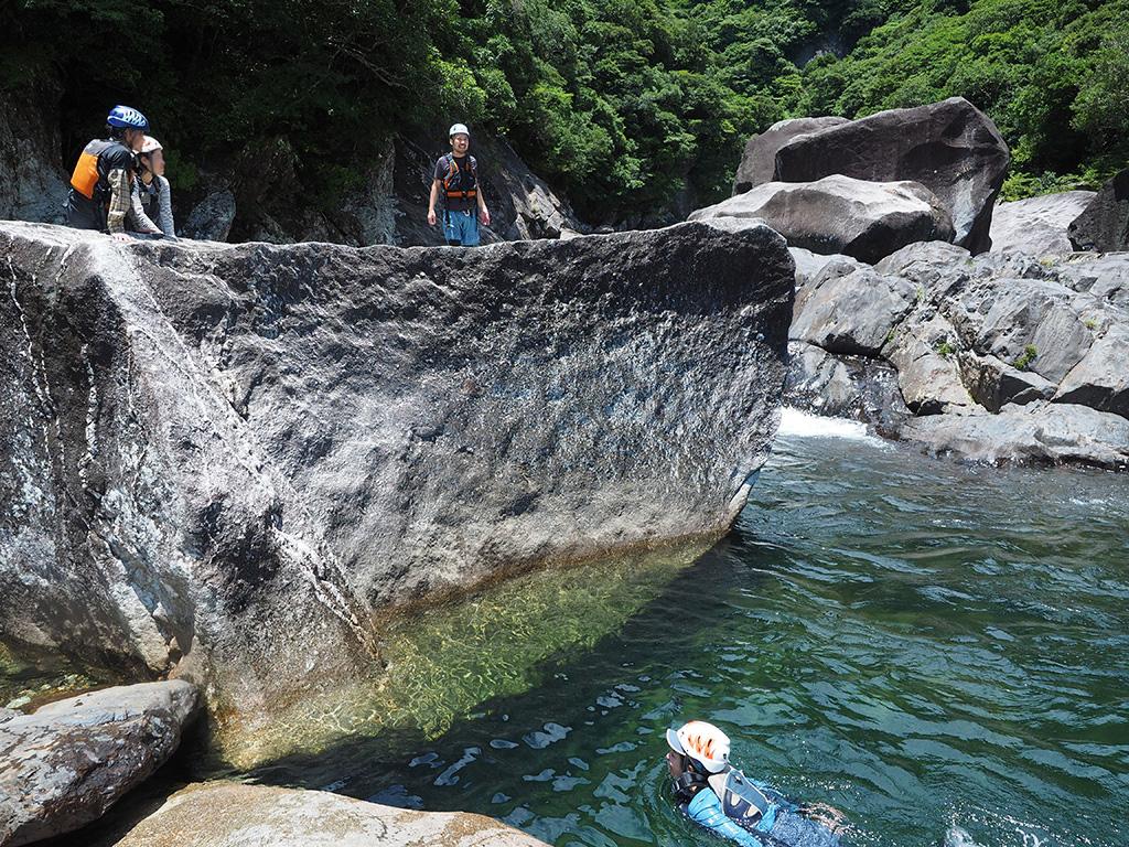 巨岩から飛び込む準備をする者、それを見守る者、ジャンプして水の中から見守る者という構図の写真