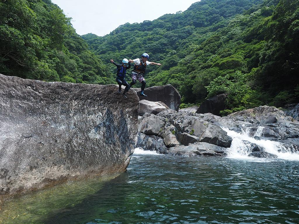 長男の背中をソッと押してあげるかの如く、大岩の上からのジャンプを一緒に飛んであげるお父さんと息子の写真