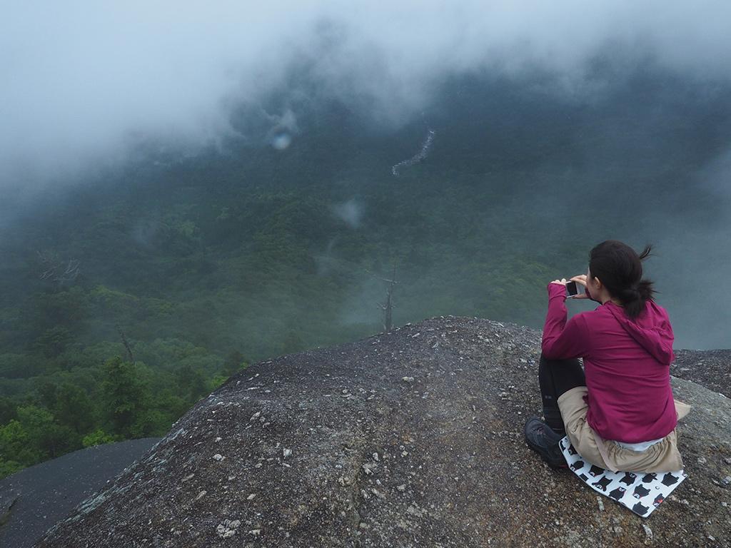 雲の切れ間から景色が突然広がる太鼓岩からの景色を眺める参加者の写真