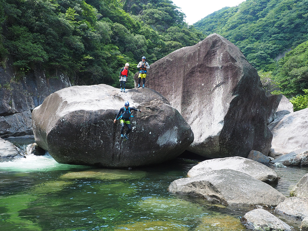 巨岩の上からジャンプを決めるYっさんと、それを岩の上から見守る3人