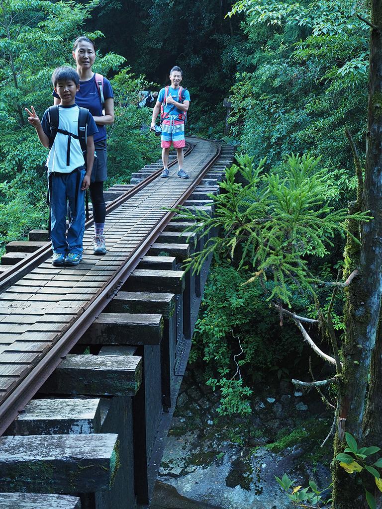 ちょっと高度感があり、手すりの無い鉄橋の上で、家族3人の写真