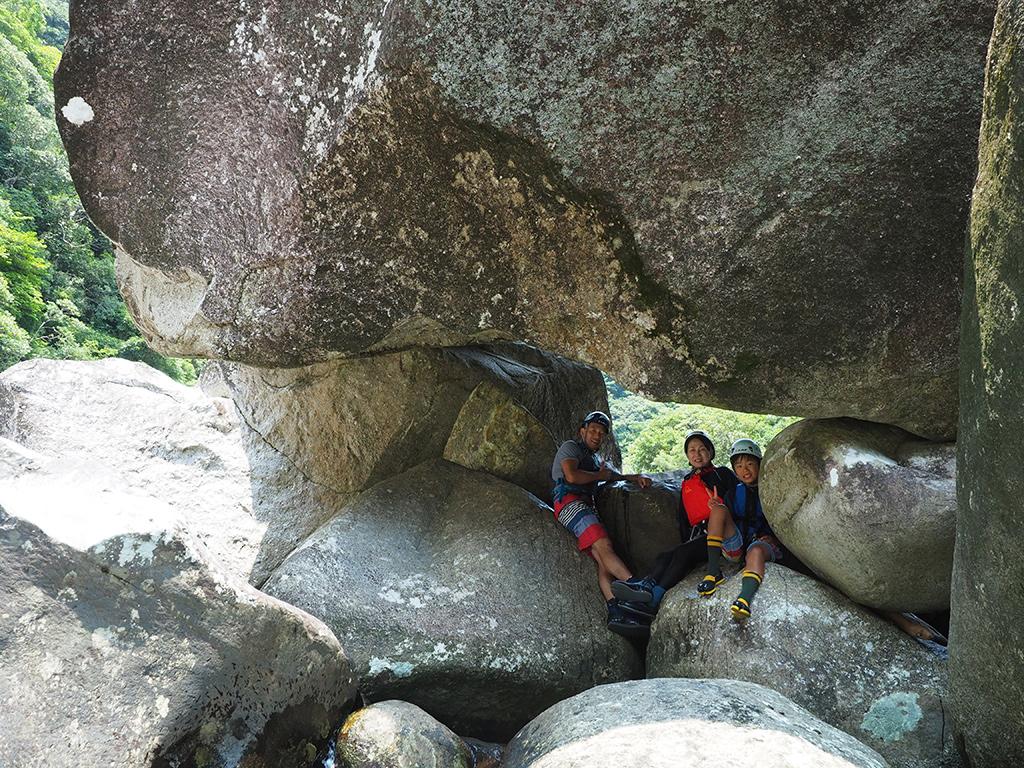 超巨大な岩の隙間から家族3人がこちらを見ている写真