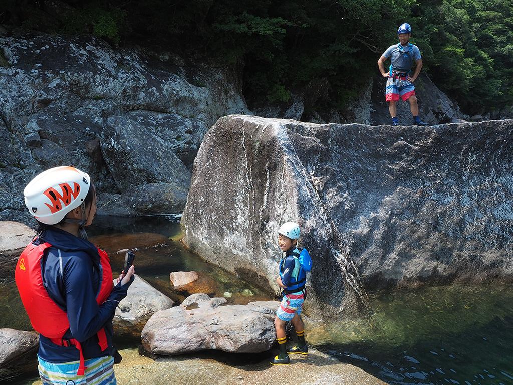 ジャンプ台としてよく遊ぶ大岩の上に立つお父さんのKさんと何とかあがりたいK君、そして応援するお母さんの写真
