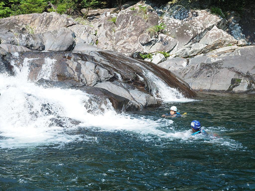 天然のウォータースライダーを滑ったあとは、水しぶき舞う落ち口を泳ぐKさんとK君の写真
