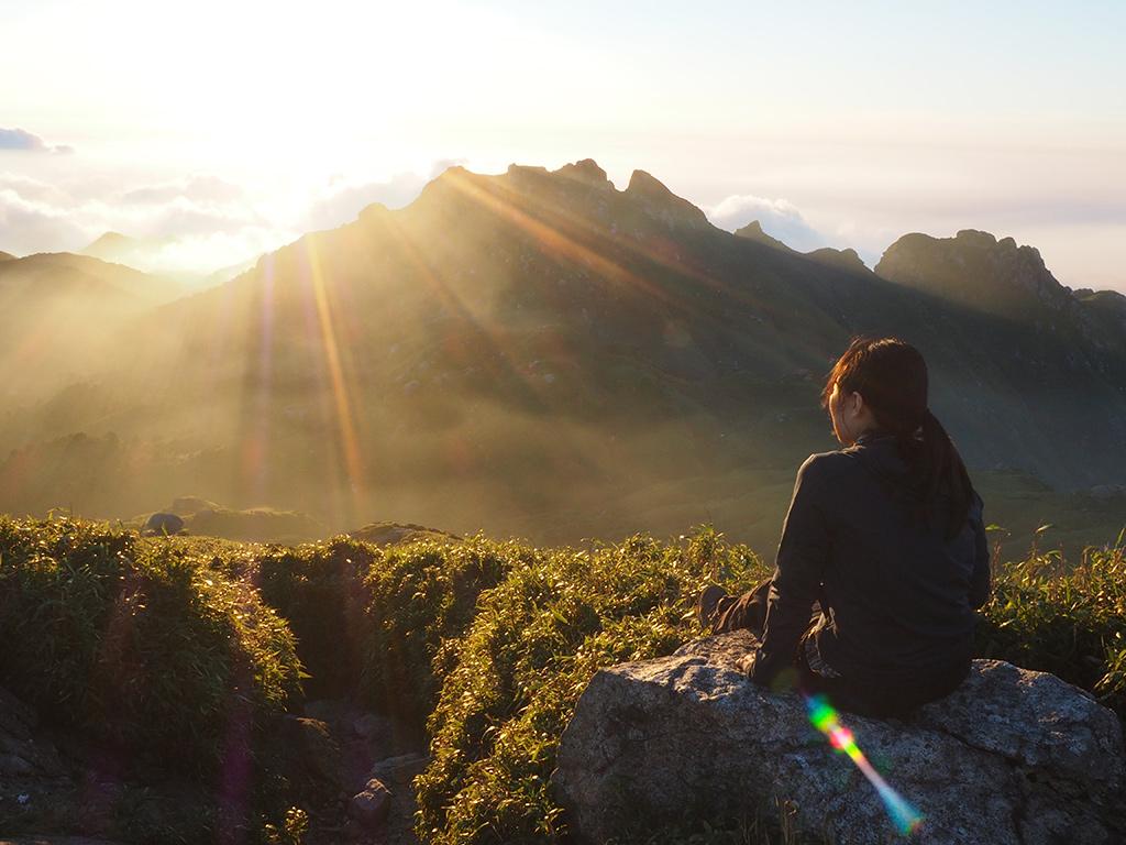 永田岳越しに見る落ち行く夕陽とそれを見つめる参加者Sさんの写真